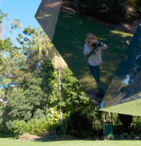 Katrina Coombs reflection from a mirrored sculpture in a botanical gardens